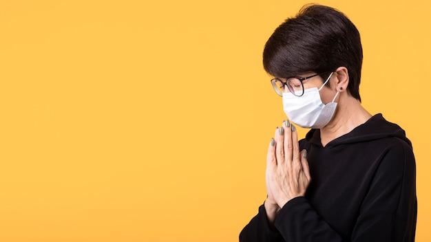 コピースペース付きの医療用マスクを着用しながら瞑想する女性 Premium写真