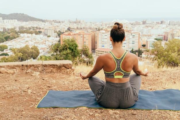 バックグラウンドで街と瞑想する女性 無料写真