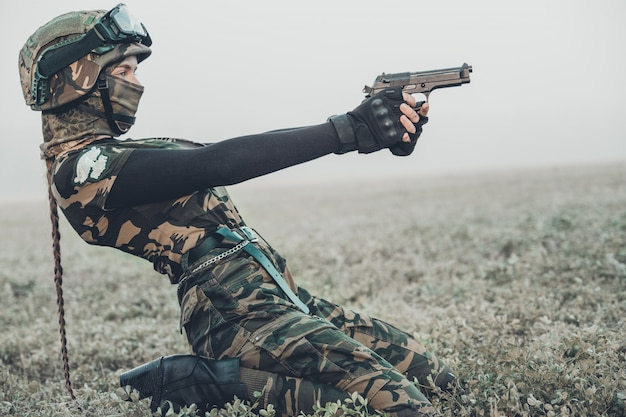 Woman in military clothes with a gun in her hands Premium Photo