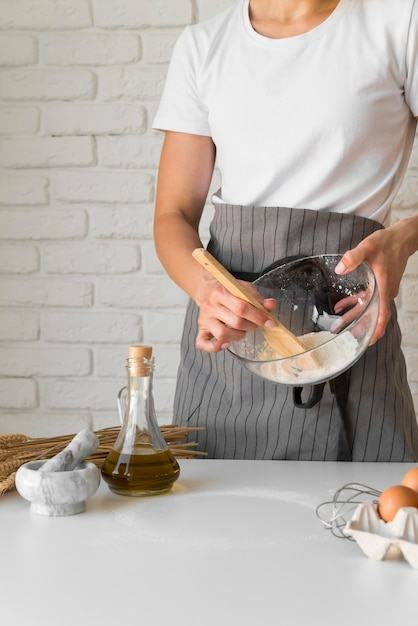 Woman mixing ingredients in bowl with wooden spoon Free Photo