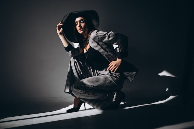 Woman model in a business suit wearing a hat Free Photo