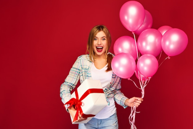 Woman model celebrating and holding box with gift present and pink air balloons Free Photo