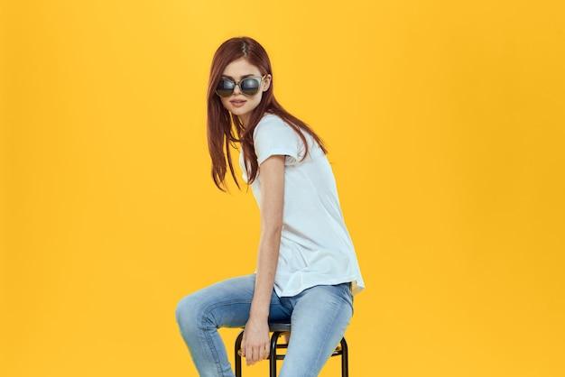 Модель женщины в джинсах и белой футболке позирует на цветном пространстве Premium Фотографии