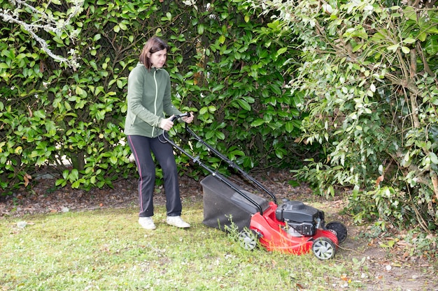Woman mows the lawn between the trees in her garden Premium Photo