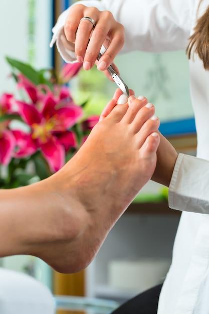Woman in nail studio receiving pedicure Premium Photo