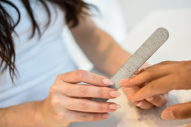 Woman in a nails salon receiving a manicure with nail file Free Photo