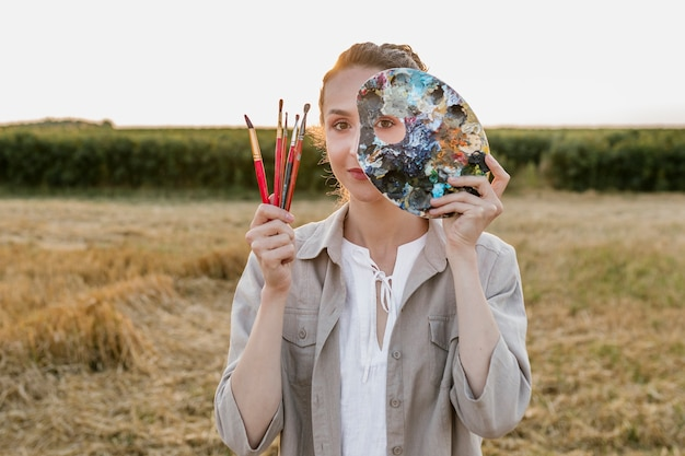 Woman in nature holding painting elements Free Photo