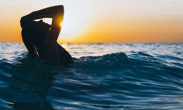 Woman in the ocean in the sunset time Free Photo