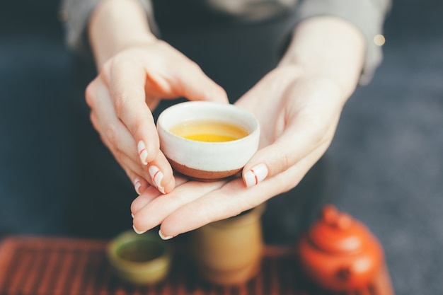 Woman offers hot tea in a vintage ceramic cup. Premium Photo