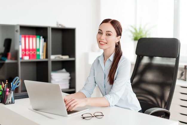Woman in the office at the desk with laptop smiling Premium Photo