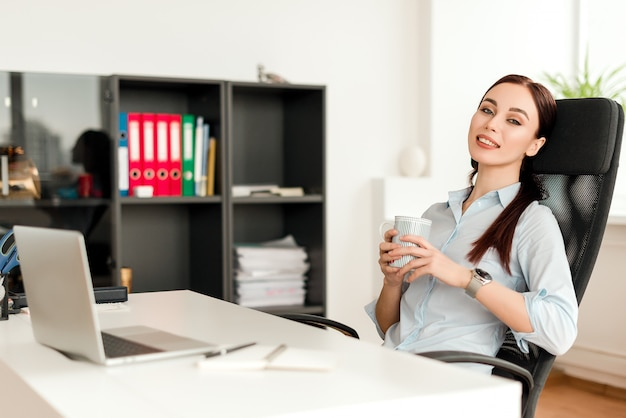 Woman in the office at a workplace behind her desk working and drinking cup of tea Premium Photo