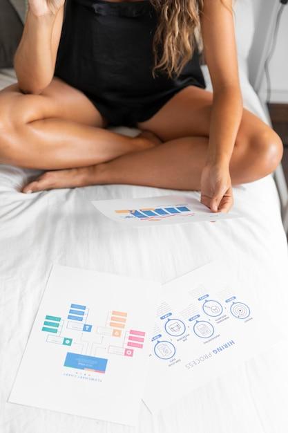 Женщина на кровати с бумажными диаграммами Бесплатные Фотографии