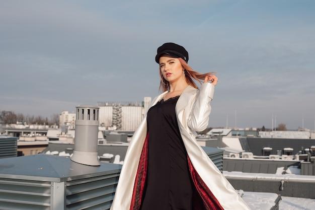 추운 겨울 태양 광선에 푸른 하늘에 대 한 건물의 지붕에 여자. 그녀는 검은 색 슬립 드레스, 빨간 안감과 모자가 달린 흰색 망토를 입고 있습니다. 그녀의 빨간 머리카락을 바람에 유지 프리미엄 사진