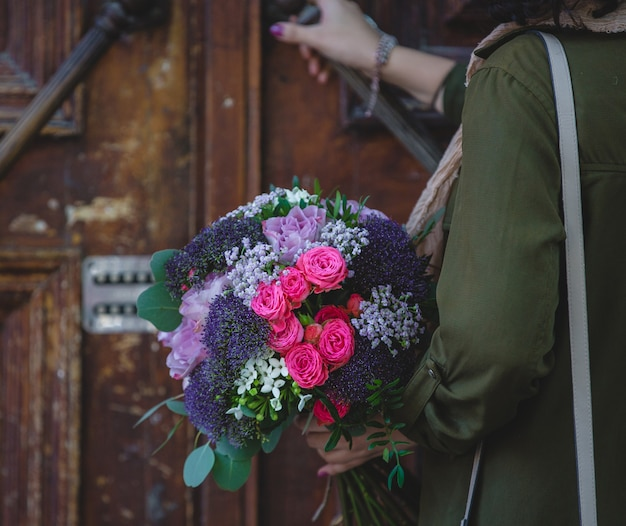 A woman opening, pushing the door with a bouquet of flowers on the other hand Free Photo