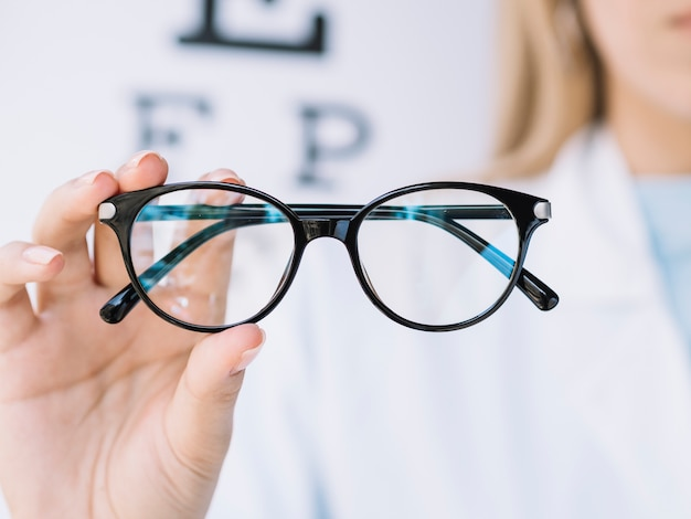 Woman ophthalmologist showing to the camera a pair of eyeglasses Free Photo