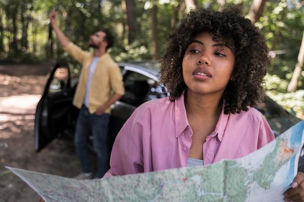 Donna all'aperto che tiene la mappa mentre il ragazzo prende selfie accanto all'auto Foto Gratuite
