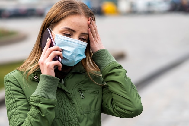 Woman outdoors wearing a mask and talking on the mobile phone Free Photo