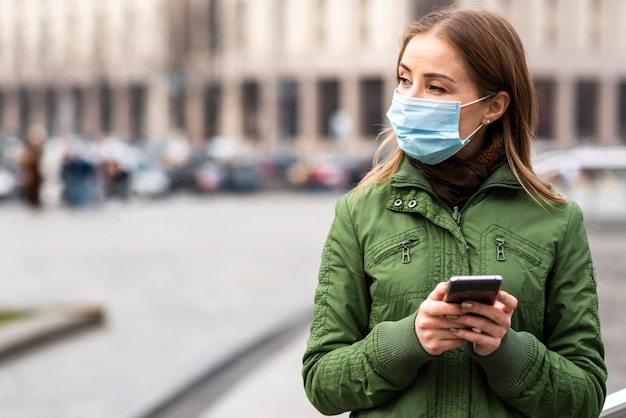 Woman outdoors wearing a mask and using the smartphone Free Photo