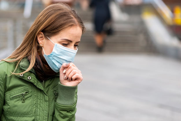 Woman outdoors wearing a protection mask and cough Free Photo