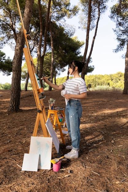 キャンバスに絵を描く自然の外の女性 無料写真
