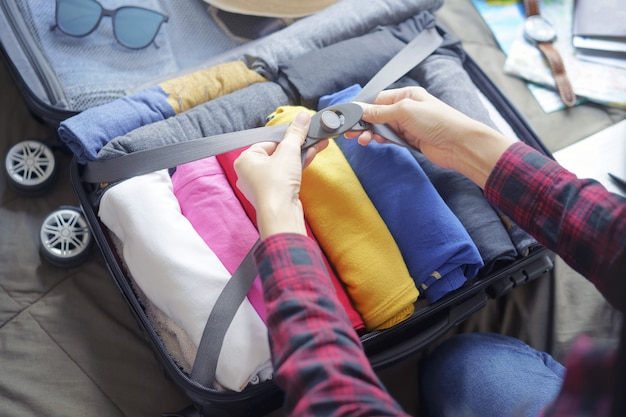 Woman pack clothes in suitcase bag on bed, prepare for new journey and travel to long weekend trip. Premium Photo