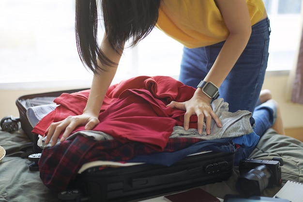 Woman pack clothes in suitcase bag on bed Premium Photo