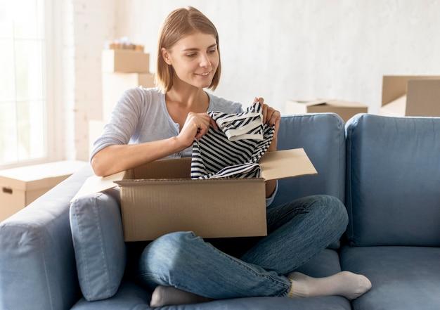 Женщина упаковочная коробка с одеждой для переезда Бесплатные Фотографии