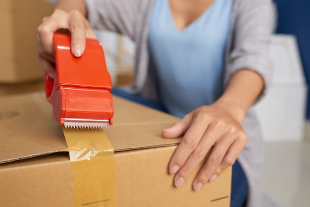 Woman packing box with tape Free Photo