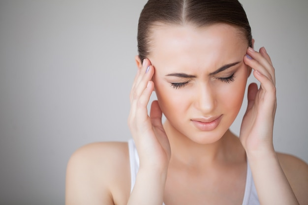 Woman in pain feeling bad and sick, having headache and fever, holding hand on forehead. beautiful unhappy tired girl suffering from painful head ache and stress. healthcare. high resolution Premium Photo