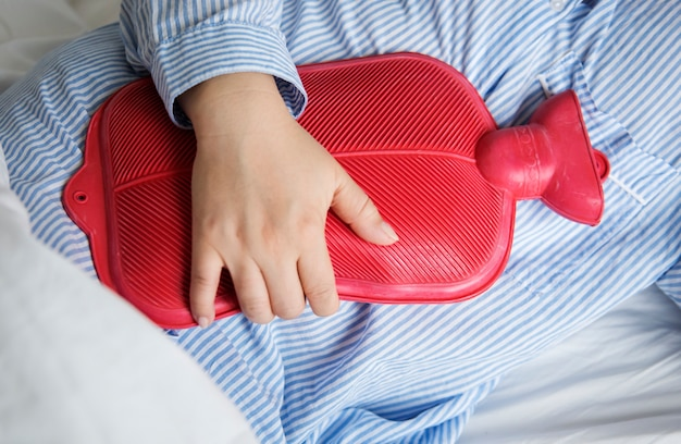 A woman in pain holding a hot water bottle Free Photo