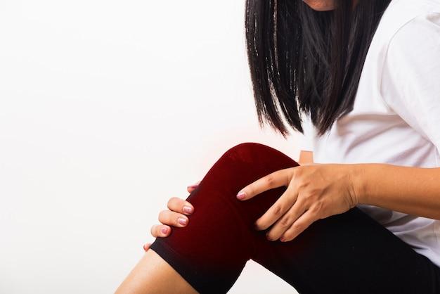 Женщина испытывает боль в колене, и она использует боль в суставах Premium Фотографии