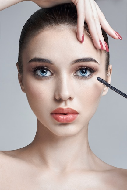 Woman paint eyes and eyelashes brush for eyelashes Premium Photo