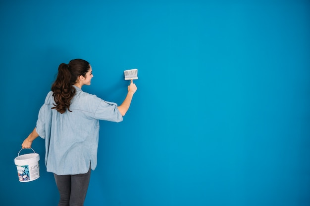 Woman painting blue wall Photo Free Download