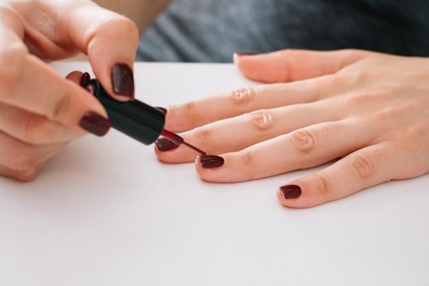Woman painting nails Free Photo