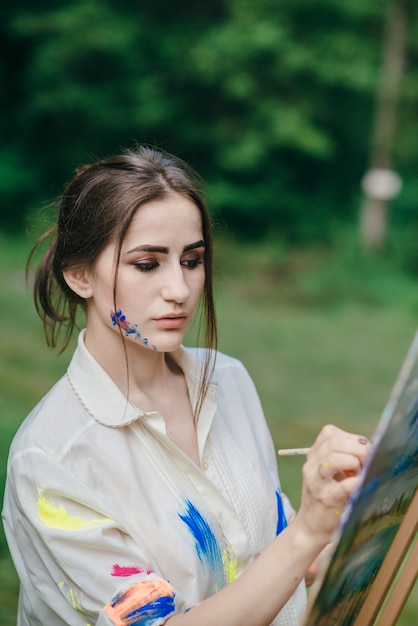 woman painting on a canvas photo free download