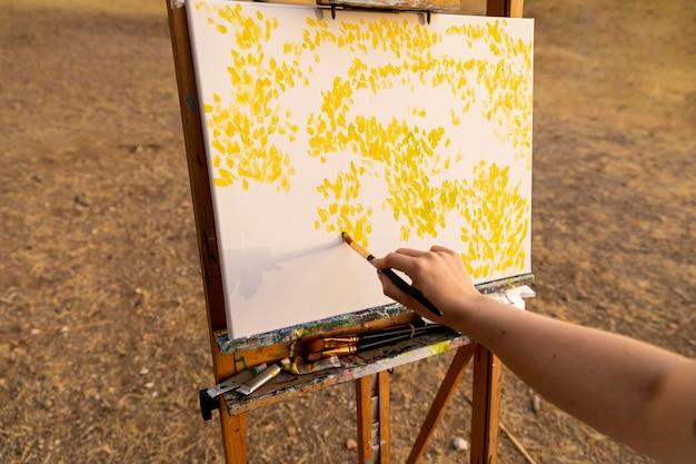 屋外のキャンバスに絵を描く女性 無料写真