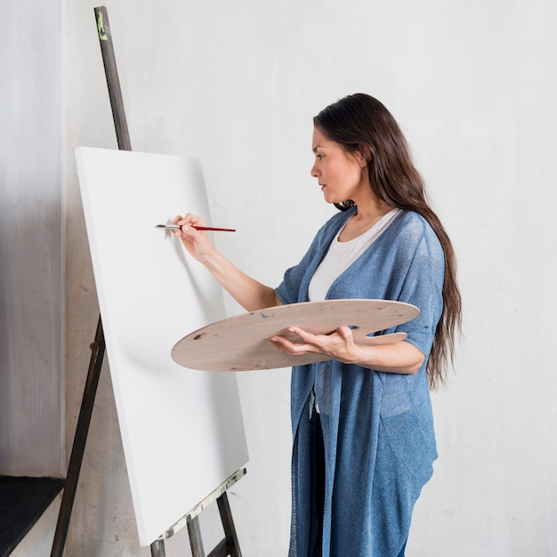 Woman painting on canvas Free Photo