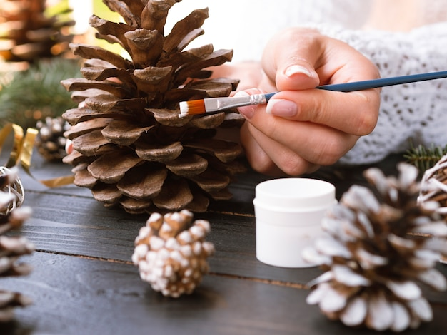 Woman painting pine cone with white paint Free Photo