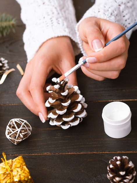 Woman painting a pine cone Free Photo