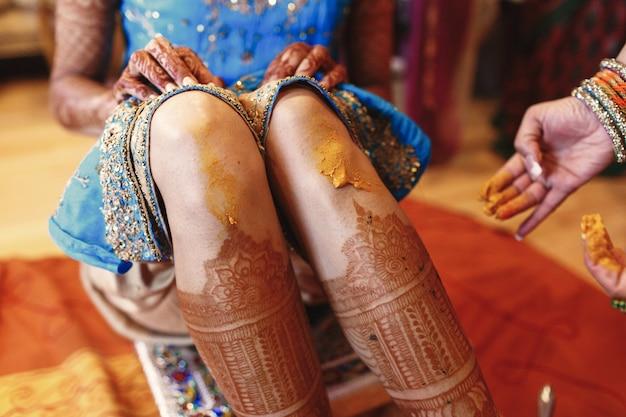 Женщина рисует колени невесты с куркумой Бесплатные Фотографии