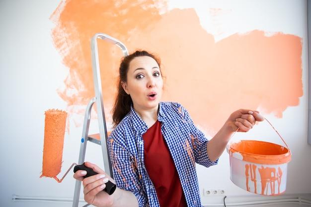 Женщина красит стену Premium Фотографии