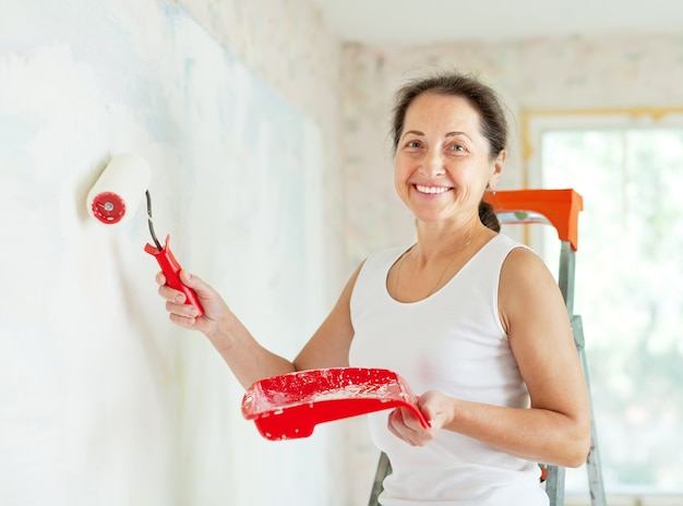 Woman paints wall with roller Free Photo