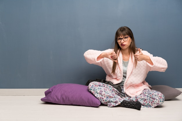 Woman in pajamas on the floor making good-bad sign. undecided between yes or not Premium Photo