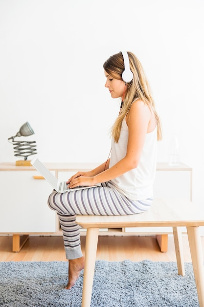 Woman in pajamas sitting with laptop and headphones Free Photo