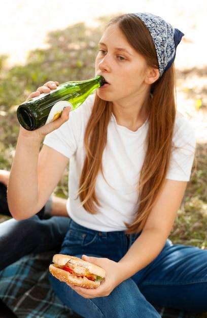 Donna al parco che beve birra e mangia hamburger Foto Gratuite
