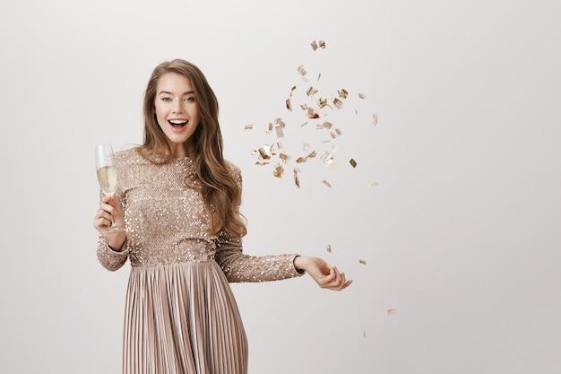 Женщина вечеринки в вечернем платье, пьют шампанское и бросают конфетти Бесплатные Фотографии