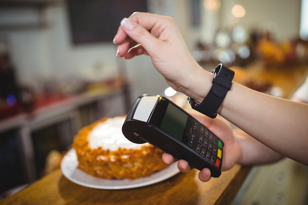 Woman paying bill through smartwatch using nfc technology Free Photo