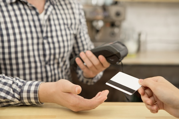 Woman paying with a credit card at the cafe Premium Photo
