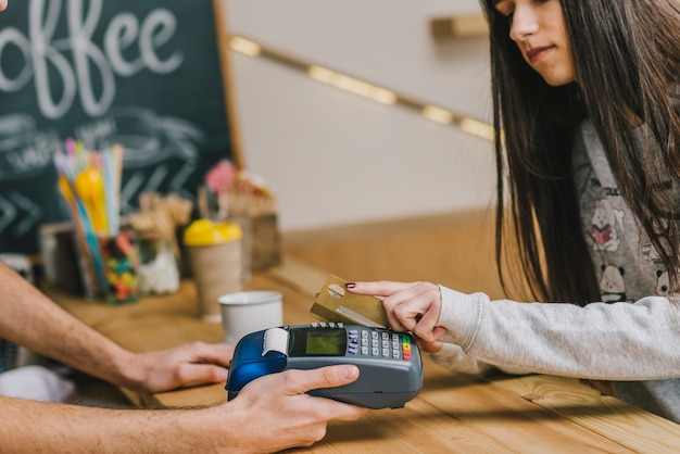 Woman paying with credit card in cafe Free Photo