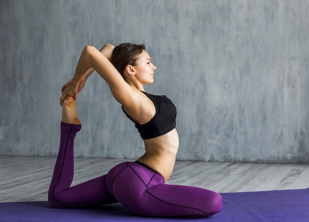 Woman performing a one-legged king pigeon pose Free Photo